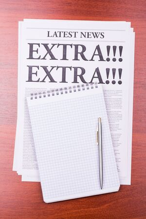 The newspaper LATEST NEWS with the headline EXTRA! EXTRA! and notepad and notepad photo