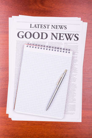 The newspaper LATEST NEWS with the headline GOOD NEWS and notepad photo