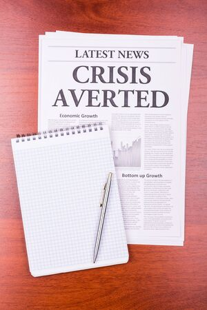 The newspaper LATEST NEWSwith the headline CRISIS AVERTED and notepad photo