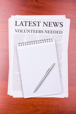 The newspaper LATEST NEWSwith the headline VOLUNTEERS NEEDED and notepad