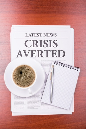 The newspaper LATEST NEWSwith the headline CRISIS AVERTED  and coffee photo