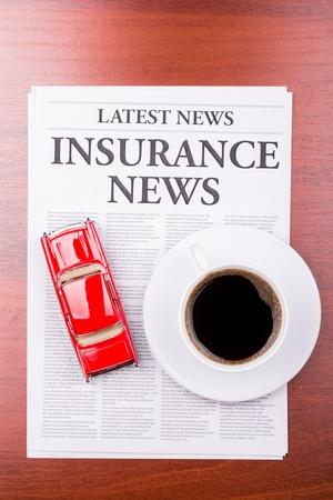 The newspaper LATEST NEWSwith the headline  INSURANCE NEWS and auto photo