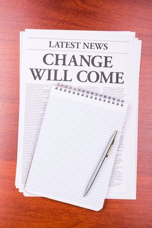 The newspaper LATEST NEWS with the headline CHANGE WILL COME and notepad photo