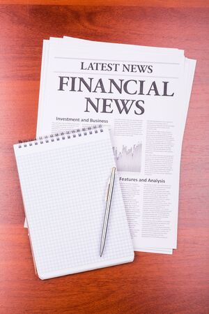 The newspaper LATEST NEWS with the headline FINANCIAL NEWS and notepad photo