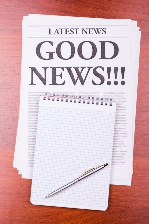 The newspaper LATEST NEWS with the headline GOOD NEWS!!! and notepad