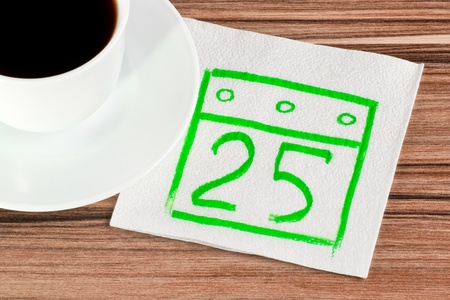 Calendar on a napkin and cup of coffee photo