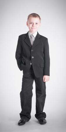 Boy in a black suit on gray background Stock Photo - 19262379
