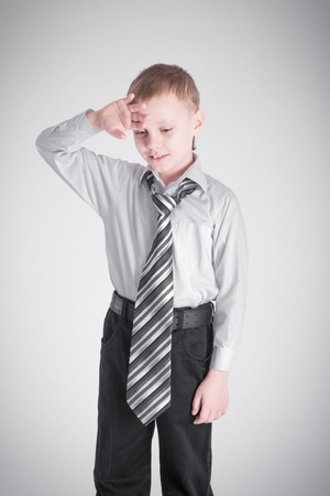 Boy with a long tie is holding his hand to his forehead photo