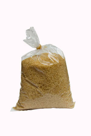 brown granulated sugar in plastic bag for selling isolated in white background photo