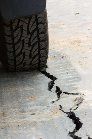 back view of tire tread and cracked asphalt photo