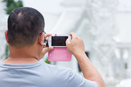 fat man taking a photo of a temple in Thailand, with mobile phone photo