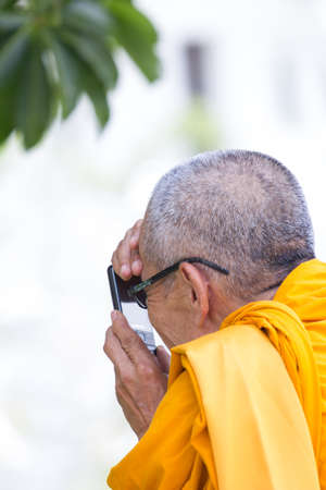 monk taking a picture with mobile phone in Thailand photo
