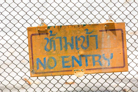fencing wire: old no entry sign on mesh wire for fencing background. Thai language means No Entry