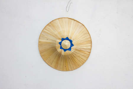 conical hat: traditional palm hat for asian farmers on white wall