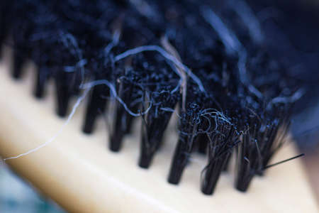 chemo: Close-up of a brush with lost hair on it, with shallow depth of field.