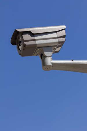 paranoia: CCTV security camera, blue sky background.
