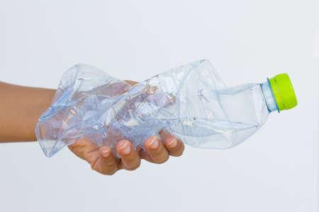 Hand holding used plastic bottle isolated on white background.