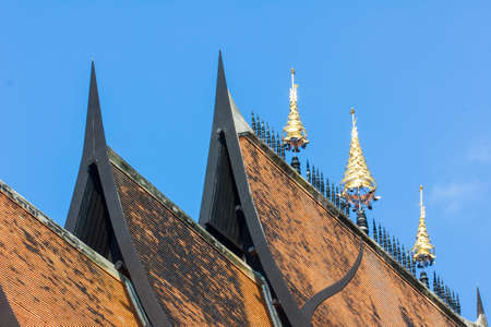 Thai art on roof Church at Thai temple in blue sky background photo
