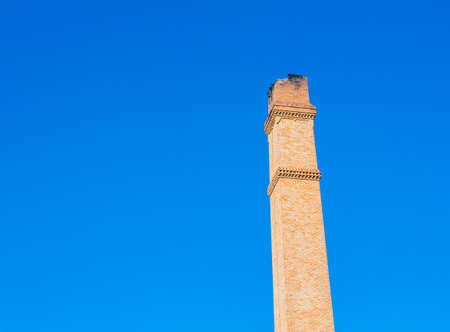 Old brick chimney on the background of clear  blue sky. photo