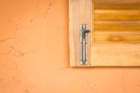 deteriorated: vintage window latch on a classic timber window panel, on orange grungy wall Stock Photo