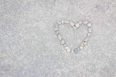 Heart made of stones on concrete background, with copyspace Foto de archivo
