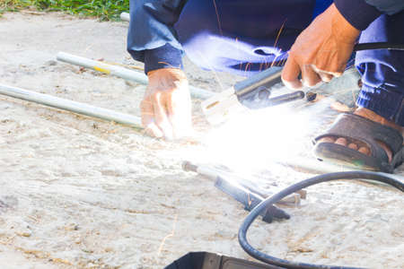 welded: Worker welding the steel part by manual without safety, danger concept