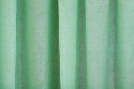 Close-up view of bright green curtain. Textured abstract backgrounds and wallpapers. Materials and textiles.