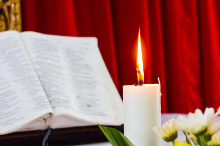 relict: bible open on a table with candle and red curtain as background. flower as foreground. Perfect for religion, easter and christmas themes. candle fucused