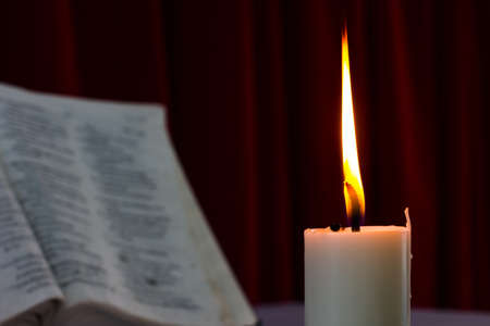 bible open: bible open on a table with candle in the dark. Perfect for religion, easter and christmas themes. candle fucused