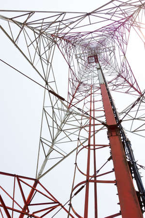 repeater: red and white color antenna repeater tower from bottom view on white sky Stock Photo