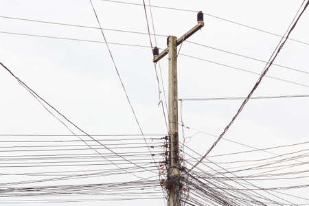 unorganized: electric post with messy wires on white sky