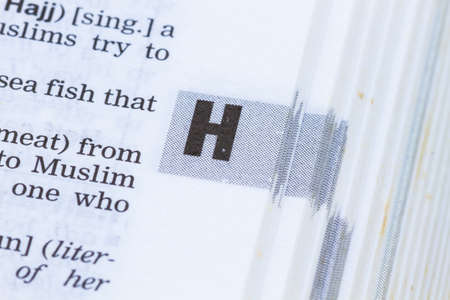 definition define: closeup letter H in dictionary, soft focus,