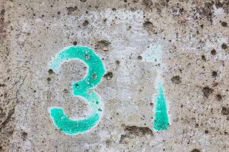 one lane street sign: green weathered number 31 on old grunge concrete wall