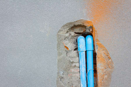 junction pipe: bury a pvc pipe in the concrete wall with copyspace on the left