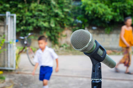 anticipated: microphone in the background of blurred outdoor with people. Stock Photo