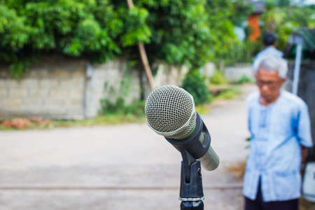anticipated: microphone in the background of blurred outdoor with old man on the left and copyspace on the right Stock Photo