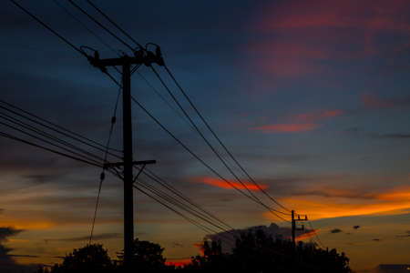 telegram: silhouette of electric post and wires in the background of twilight sky.