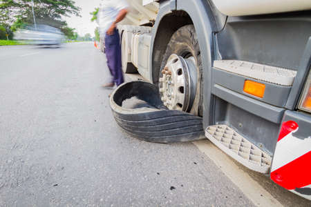 Damaged 18 wheeler semi truck burst tires by highway street, with blurred driver.