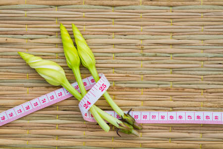 moonflower: Ipomoea alba L. on traditional mat with measuring tape, diet concept. copyspace Stock Photo