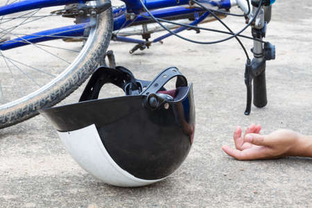 traffic accidents: bicycle and a helmet lying on the road with hand of human, accident concept
