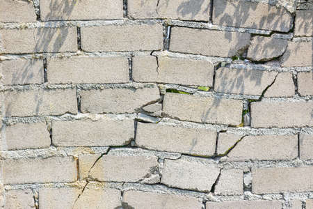 closeup of dangerous wall with cracks in sunshine. Stock Photo