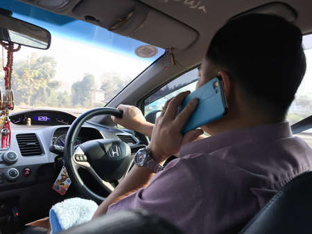 telephoning: CHIANG RAI, THAILAND - FEBRUARY 12 : unidentified man telephoning with mobile phone or smartphone while driving car on February 12, 2016 in Chiang rai, Thailand Editorial