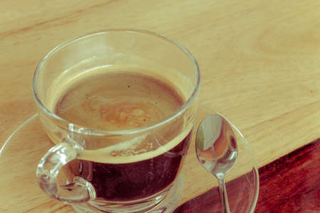 glass cup: Black expresso coffee in small glass cup on wooden table with teaspoon, vintage retro style.