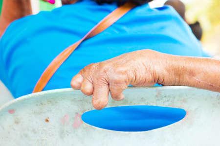 lepra: primer plano la mano del hombre de edad que sufre de lepra en el respaldo de la silla de plástico.