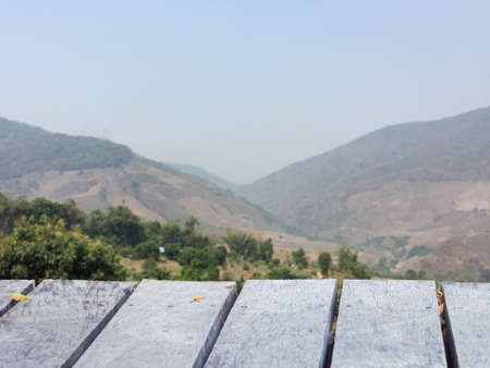 deforested: wooden table perspective with blurred deforested mountain and sky background