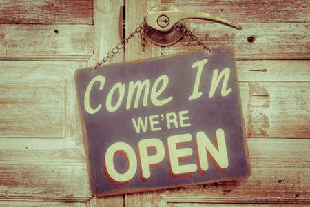 Venite siamo aperti sulla porta di legno, stile retrò vintage