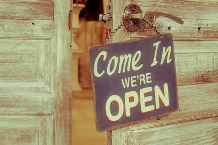 come in: BANGKOK, THAILAND - DECEMBER 20: Come In Were Open on the wooden door open on December 20, 2015 in Bangkok, Thailand. Vintage retro style.