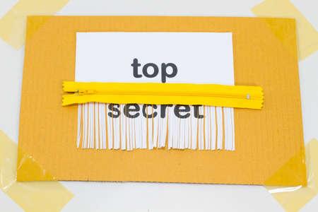 paper shredder: Top Secret, destroying sheet of paper with yellow zipper as a shredder.