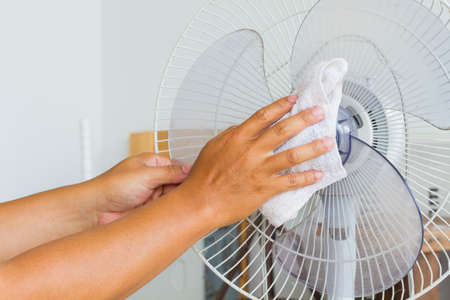 electric fan: Close up horizontal photo of male hand cleaning dirty electric fan blade with cloth.