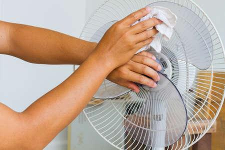 Cierre de la foto horizontal de limpieza de la mano masculina aspa del ventilador eléctrico sucia con un paño. Foto de archivo